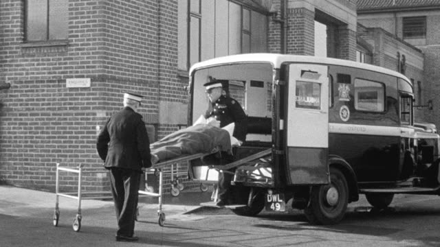 1949 TS Emergency personnel transporting polio patient from ambulance to gurney and wheeling towards the hospital entrance / United Kingdom