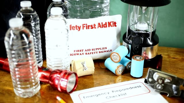 emergency preparedness natural disaster supplies.  water, flashlight, lantern, radio, batteries, first aid kit. - survival stock videos & royalty-free footage