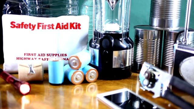 emergency preparedness natural disaster supplies.  water, flashlight, lantern, radio, batteries, first aid kit. - can opener stock videos and b-roll footage