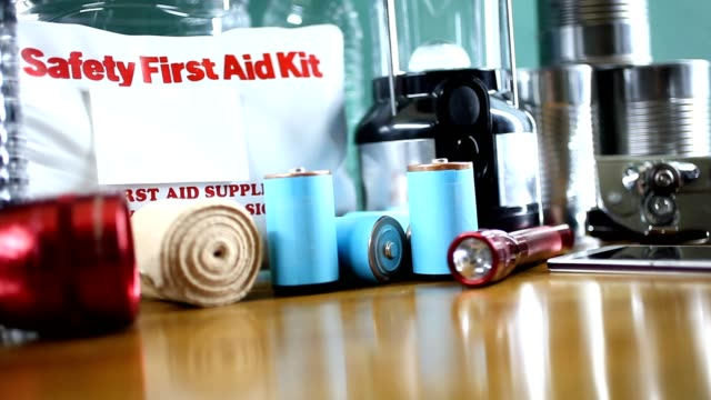 emergency preparedness natural disaster supplies.  water, flashlight, lantern, radio, batteries, first aid kit. - electric torch stock videos & royalty-free footage