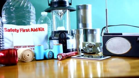 emergency preparedness natural disaster supplies.  water, flashlight, lantern, radio, batteries, first aid kit. - emergency planning stock videos & royalty-free footage