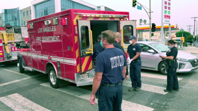 emergency response - los angeles police department officers and fire department help car accident victim in los angeles, california, 4k - rescue worker stock videos & royalty-free footage