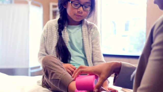Emergency room physician wraps little girl's ankle with sports tape