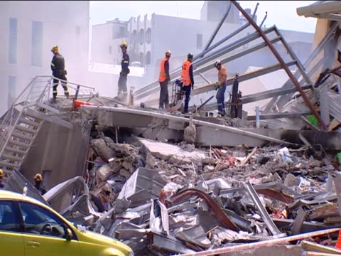 Emergency services tend to a seven story office block in ruins following the Christchurch earthquake