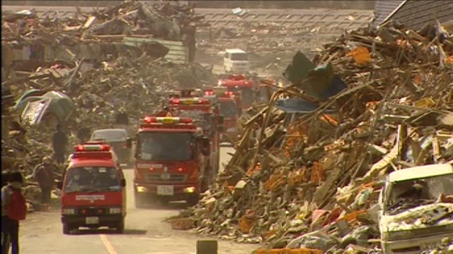 vídeos y material grabado en eventos de stock de emergency vehicles arrive at wreckage of town hit by tsunami rikuzentakata japan - maremoto