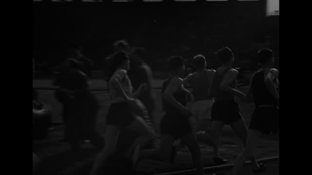 Emil Zatopek of Czechoslovakia running / start of 5000meter race / runners race past camera / people in stands watching / Zatopek running in lead /...
