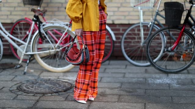 emili sindlev is seen wearing yellow jacket, bag, orange plaid pants outside mykke hofmann during the copenhagen fashion week autumn/winter 2019 -... - タータンチェック点の映像素材/bロール
