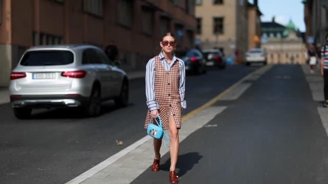 emili sindlev wearing brown sleeveless checked dress striped button shirt blue balenciaga bag with animals printed leather shoes seen during... - sleeveless dress stock videos and b-roll footage