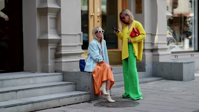 vídeos de stock e filmes b-roll de emili sindlev wearing yellow knit cardigan green wide leg pants burberry clutch and jeannette madsen wearing orange midi skirt ankle boots light blue... - calças
