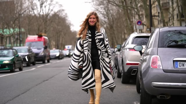 emili sindlev wears a black and white zebra pattern printed poncho long coat, a black turtleneck dress, beige leather thigh high boots, earrings,... - thigh human leg stock videos & royalty-free footage