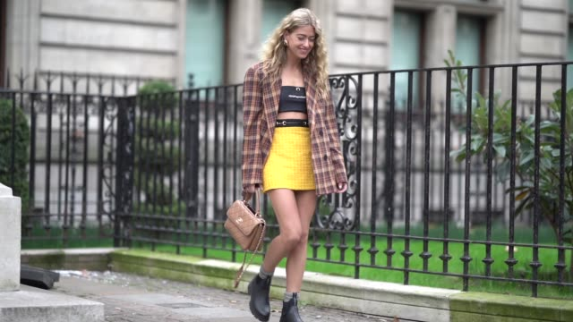 Emili Sindlev wears a brown checked blazer jacket black bras a yellow skirt a brown Chanel bag during London Fashion Week February 2019 on February...