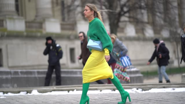 Emili Sindlev wears a green wool pull over a yellow skirt green boots a shoulder strap bag during Paris Fashion Week Womenswear Fall/Winter 2018/2019...