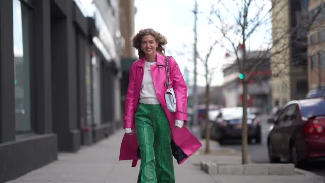 emili sindlev wears a pink crocodile pattern coat, a white bag, green snake print flared pants, a white top, outside self portrait, during new york... - ニューヨークファッションウィーク点の映像素材/bロール