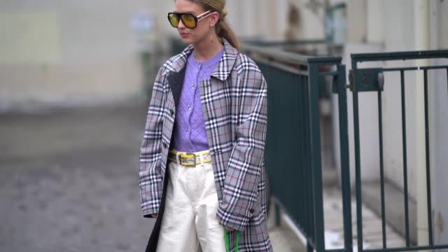 emili sindlev wears a purple shirt white flare pants a green bag yellow sunglasses a belt a tartan coat during paris fashion week womenswear... - tartan video stock e b–roll