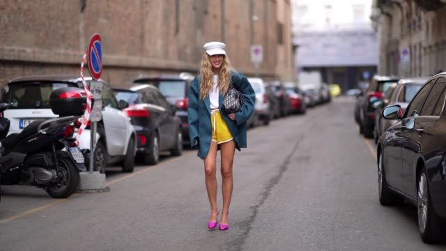 emili sindlev wears a white cap hat a green oversized blazer jacket a white tshirt a dior monogram bag yellow shorts neon pink pointy shoes outside... - shorts stock-videos und b-roll-filmmaterial