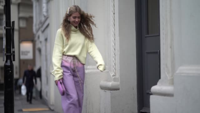 emili sindlev wears a yellow turtleneck top with oversized sleeves, pale purple flare pants, a purple clutch, white shoes, during london fashion week... - pastel colored stock videos & royalty-free footage