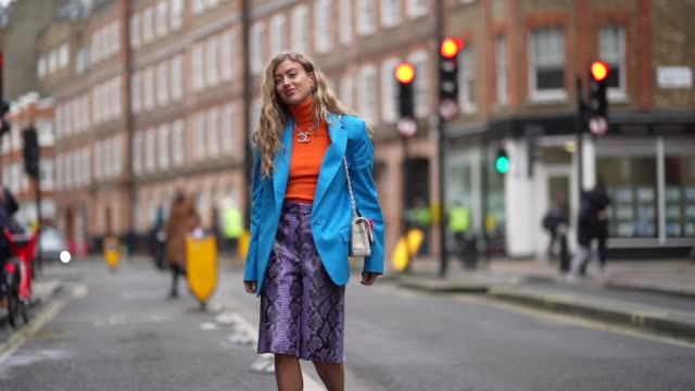 vídeos y material grabado en eventos de stock de emili sindlev wears an orange turtleneck wool pullover, a blue oversized blazer jacket, a purple snake print leather skirt, a chanel logo necklace,... - falda