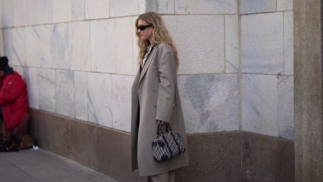 emili sindlev wears sunglasses, a gray long jacket with oversized long sleeves, a white top, a cream color shirt, a dior monogram bag, flared pants,... - gray jacket stock videos & royalty-free footage
