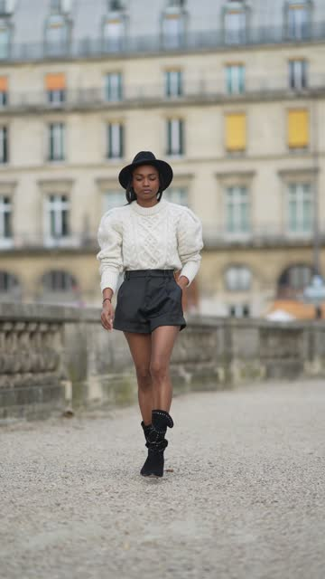 emilie joseph @in_fashionwetrust wears a black wool fedora hat, a white latte cable knit sweater with bold shoulders by isabel marant, black shiny... - shorts stock videos & royalty-free footage