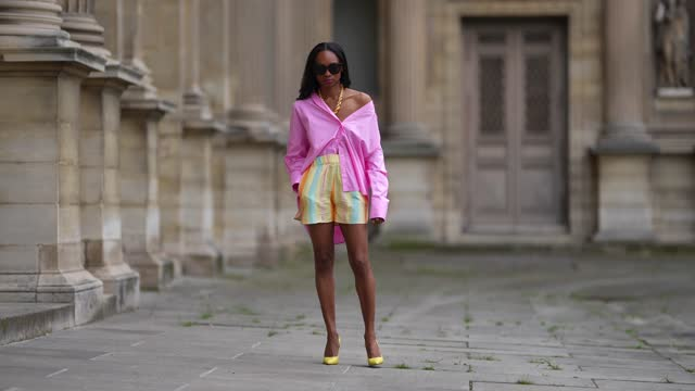 emilie joseph @in_fashionwetrust wears black sunglasses, silver earrings, a gold chunky necklace from merbabe, a pale pink oversized boyfriend shirt... - shorts stock videos & royalty-free footage