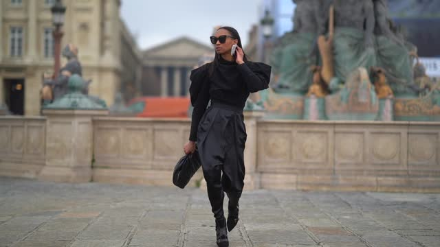 stockvideo's en b-roll-footage met emilie joseph wears black sunglasses from gentle monster, bejeweled long earrings from isabel marant, a black ruffled/gathered top with puff/balloon... - mouw