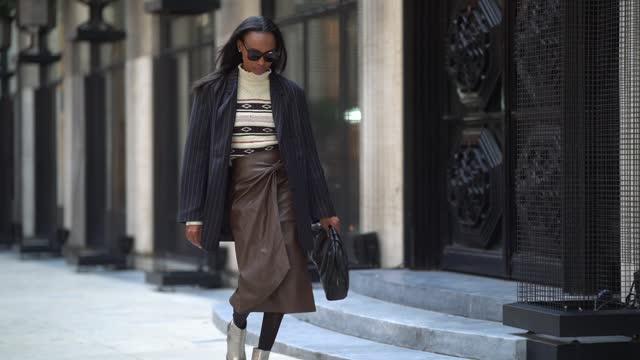 vídeos y material grabado en eventos de stock de emilie joseph wears sunglasses, a dark navy blue striped oversized blazer jacket from frankie shop, a white wool turtleneck pullover with printed... - falda