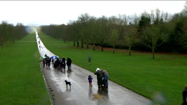 Arrival at Windsor Castle More of the same / People along in Windsor Great Park in rain / Household Cavalry on horseback through town of Windsor