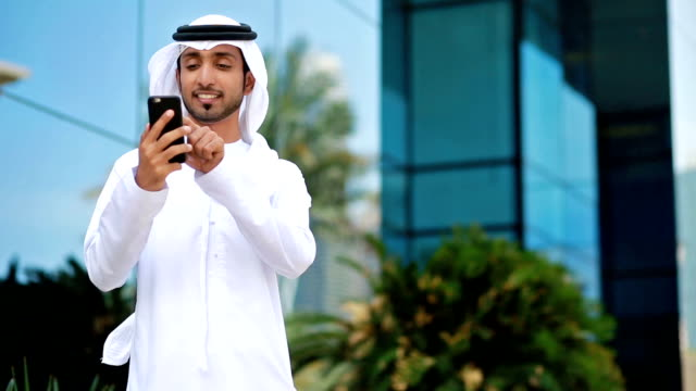 emirati businessman using phone outdoors - handheld stock videos & royalty-free footage