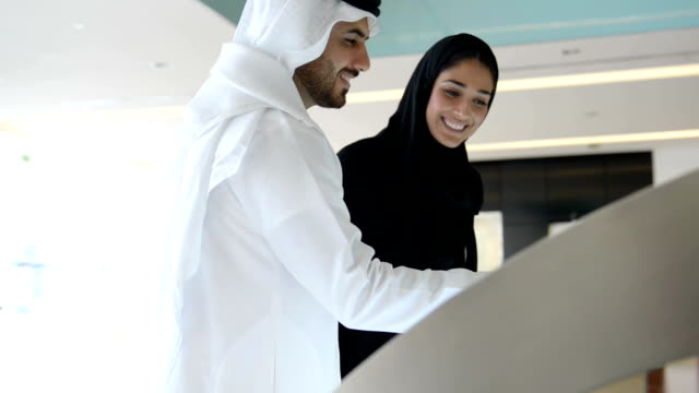 emirati couple using information display - retail stock videos & royalty-free footage