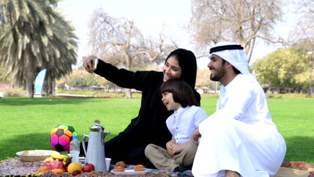 emirati family taking a selfie at picnic - family stock videos & royalty-free footage