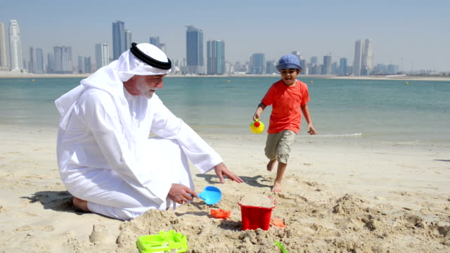 stockvideo's en b-roll-footage met emirati grandfather and little boy playing on the beach - kleinzoon