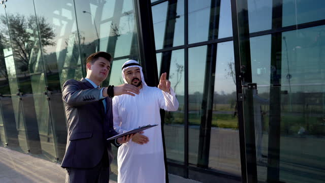 emirati man and western businessman having a business conversation - partnership stock videos & royalty-free footage