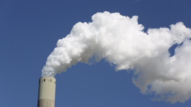 vidéos et rushes de emissions from a coal fired power plant in amsterdam, holland, with a plane flying over. - coal