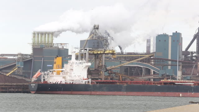 emissions from the tata steel works in ijmuiden near amsterdam, netherlands, with a ship unloading coal - olanda settentrionale video stock e b–roll