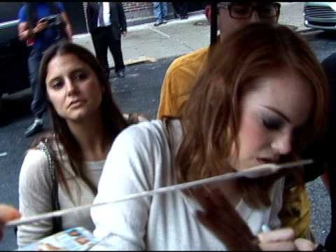 Emma Stone tries her best to sign autographs in the rain as she departs the 'Late Show With Davd Letterman' in New York 08/03/11
