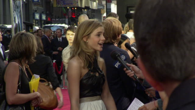 Emma Watson standing on crowded red carpet outside Ziegfeld Theater talking to press