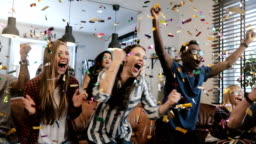 Emotion. Multi-ethnic fans celebrate winning. Confetti 4K slow motion. Passionate supporters shout watching game on TV