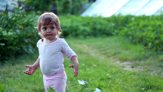 Emotional baby girl running toward the camera in the backyard