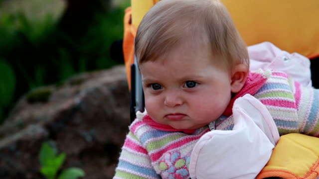 emotional baby sitting in the pram in the backyard - part of a series stock videos & royalty-free footage