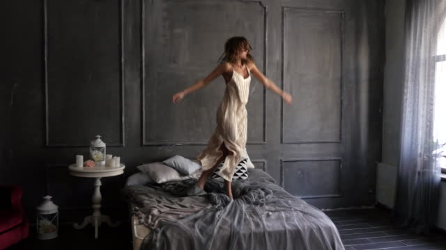 Emotional woman dancing on the bed in the morning