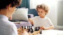 Emotional young kid playing chess with mommy moving pieces on board and smiling