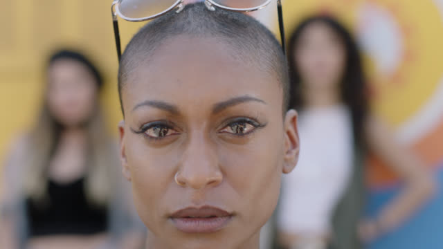 cu slo mo. emotional young mixed-race woman stares at camera as two women stand out of focus in background. - serious stock videos & royalty-free footage