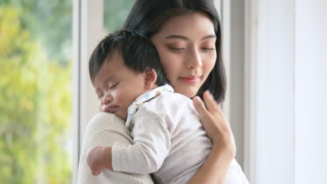 vidéos et rushes de jeune maman émotive retenant son nouveau-né. - affectueux