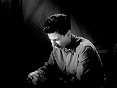 vidéos et rushes de b/w ms 1951 emotionally distressed soldier sitting in dark room / usa - solitude