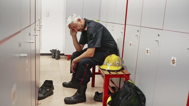 stockvideo's en b-roll-footage met emotioneel beklemtoonde mannelijke brandweermanzitting in kleedkamer - hoofddeksel