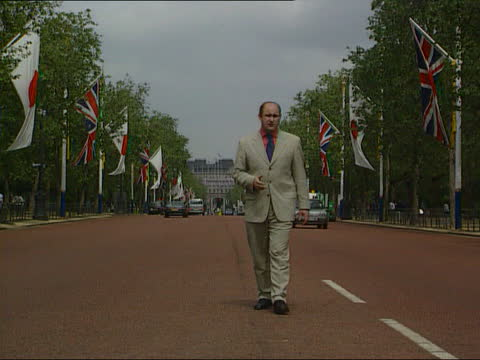 emperor akihito visit to uk; d)c5f itn england: london: the mall: ext japanese flag flying from flagpole at side of road next to british one pull out... - 日本の皇室点の映像素材/bロール
