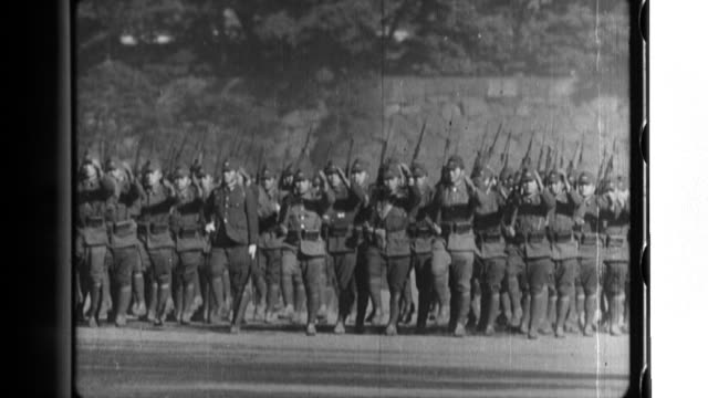 Emperor Hirohito is on horseback as he salutes Imperial Japanese Army infantry artillery and cavalry units as they parade at the New Year Army Review