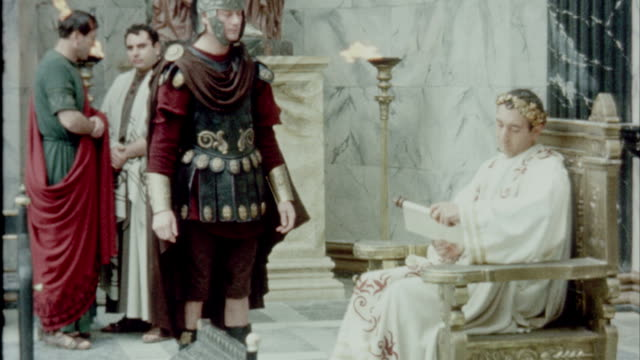 emperor trajan sitting on throne looking at scroll document and speaking with civil servants recreation emperor trajan in ancient rome on january 01... - återskapande bildbanksvideor och videomaterial från bakom kulisserna