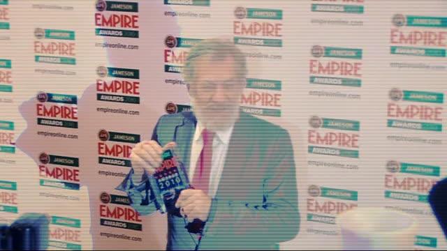 empire film awards in london; sir ian mckellen posing with award for press / patrick stewart chatting / mckellen talking to press / stewart talking... - ian mckellen stock videos & royalty-free footage