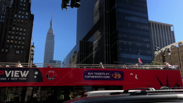 stockvideo's en b-roll-footage met empire state building and tour bus in new york city. - dubbeldekker bus